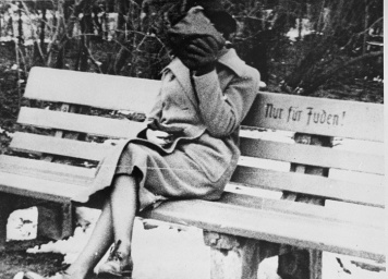 "A woman sits on a park bench marked ""Only for Jews."" Austria, ca. March 1938. US Holocaust Memorial Museum, courtesy of Wiener Library Institute of Contemporary History."